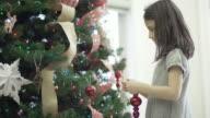Junges Mädchen dekorieren Weihnachtsbaum mit Ihrem Bruder und Mutter