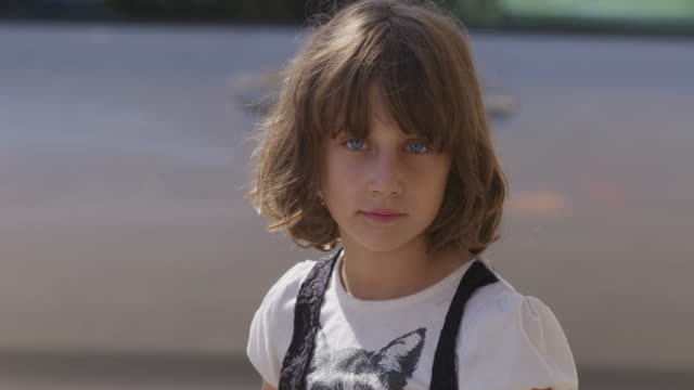 Young girl direct to camera with serious expression.