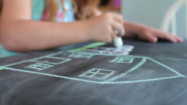 LA Young girl drawing a house and family with chalk on a table