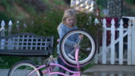 MS Young girl fixing her bicycle by herself