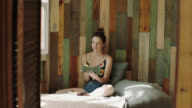 WS SLO MO. Young girl flips through pages of diary and looks up at camera in rustic sunlit bedroom.