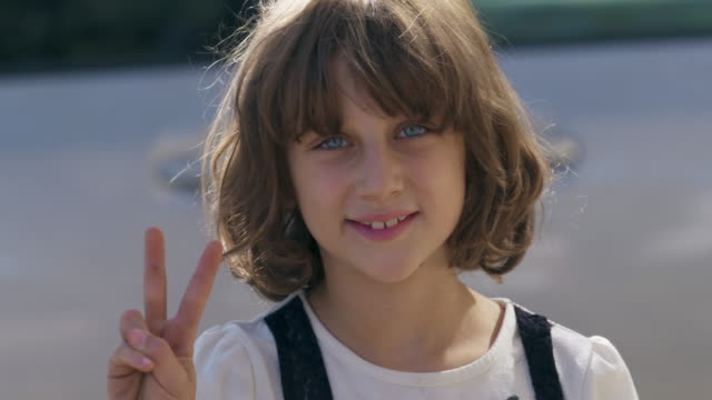 Young girl gives peace sign hand gesture to camera.