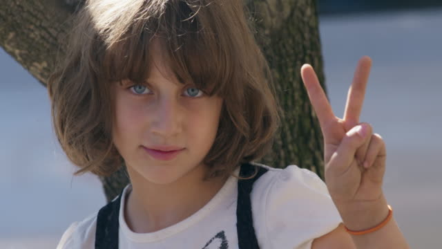 Young girl gives peace sign to the camera.