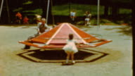 Young Girl Going down Slide / Seesaw / Roundabout / Childhood Playground on April 01 1968 in Farmington Utah