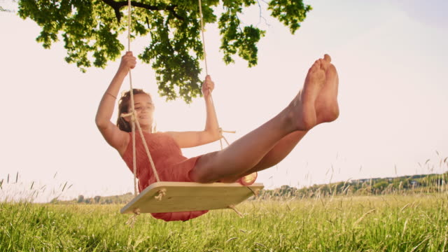 Young girl having fun swinging on a tree swing