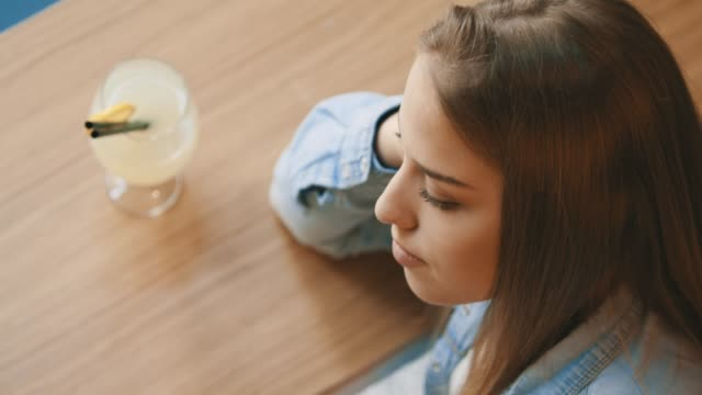 Young girl in cafe with hand on head