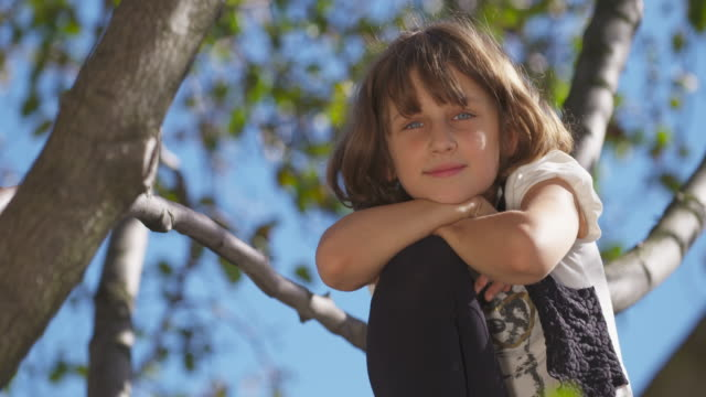 Young girl in tree rests her head on her knee and smiles