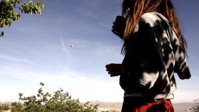 Junges Mädchen trinkt Kaffee zusehen Heißluftballons fliegen über Göreme in Kappadokien