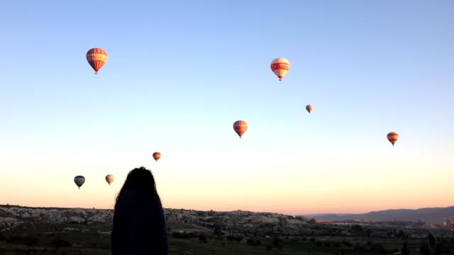 Junges Mädchen ist gerade von Heißluftballons fliegen über Göreme in Kappadokien