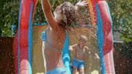 SLO MO Young girl jumping over a water sprinkler