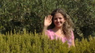 Young girl jumps out of bushes and greets someone