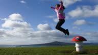 Young girl jumps over magic mushroom
