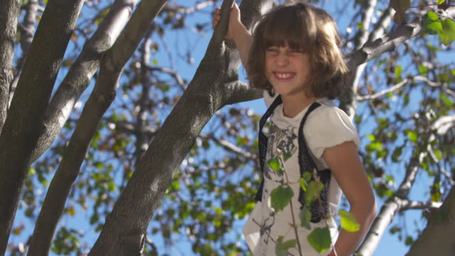 Young girl laughs to camera as she plays in tree.