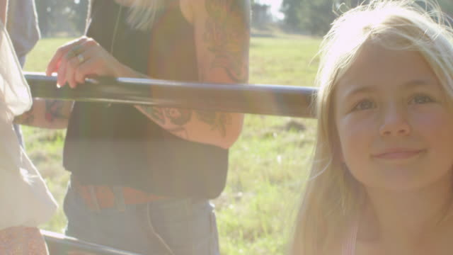 MS Young girl leaning on fence gate in field at sunset with friends