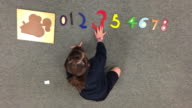 Young girl learns to count numbers