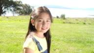 SHAKY MS Young girl looking into distance, turning, and smiling at camera / San Francisco, California, 2008