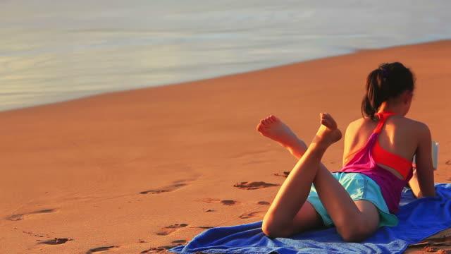 Junges Mädchen auf dem Bauch liegen tropischen Strand lesen Buch