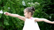 Young girl making bubbles, slow motion