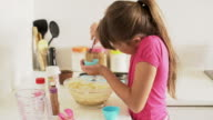MS young girl making cup cakes at home.