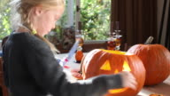 young girl making halloween pumpkin, boy in the background