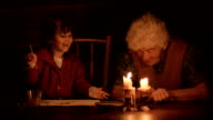 A young girl painting with her grandmother by the light of candles