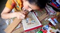 A young girl paints a bird. Folk art of Uzbekistan.