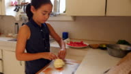 MS Young girl placing tomatoes and mozzarella on plate to make caprese salad
