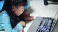 Young Girl playing on Labtop computer