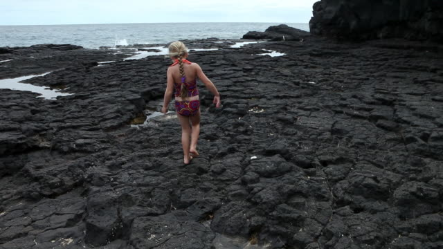MS TU Young girl playing on rocky shoreline / Kauai, Hawaii, United States