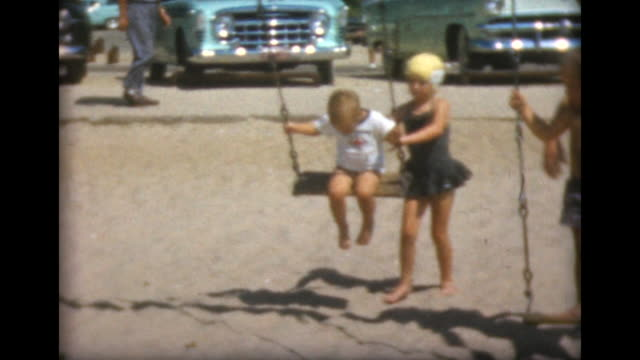 1957 young girl pushes young boy on beach swing