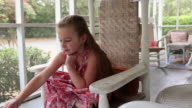 MS Young girl reading book on screened porch / St. Simon's Island, Georgia, United States