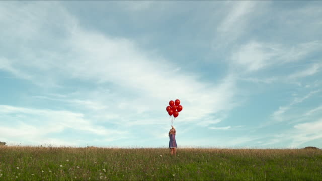 MWS young girl releasing small bunch of  balloons in field