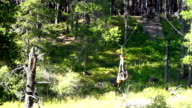 Young girl riding zip line across ravine upside down