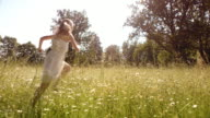 SLO MO Young girl running in high grass on a sunny day