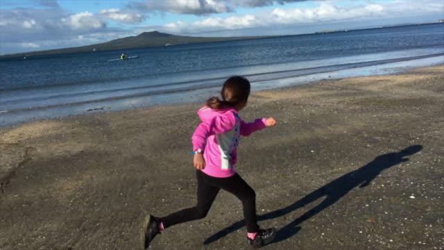 Young girl runs on a beach