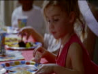 Young Girl Sits at a Table Eating Cake and Crisps From a Disposable Plate at a Birthday Party