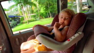 MS PORTRAIT young girl sitting in car seat in minivan + looking at camera / Florida