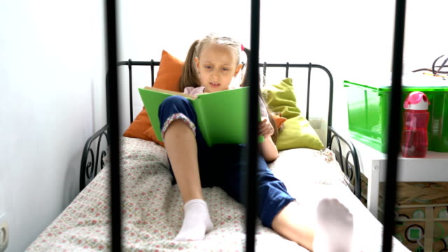 Young girl sitting on the bed and reading her text book
