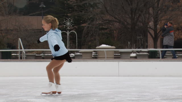 A young girl skating at a busy rink