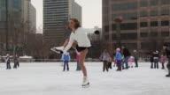 A young girl skating at a busy rink
