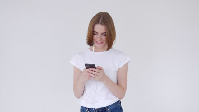 Young girl smiling while texting on cellphone