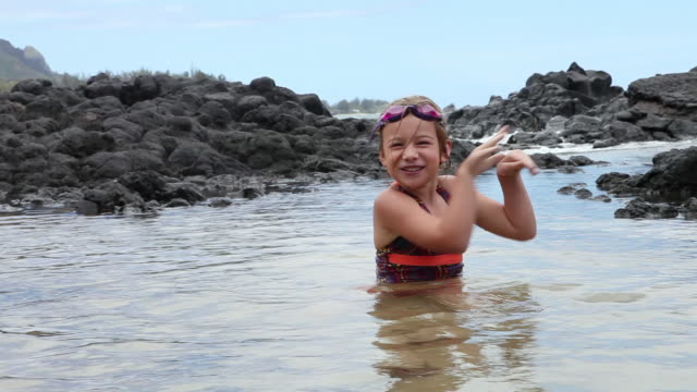 MS Young girl swimming with playing in ocean / Kauai, Hawaii, United States