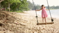 WS Young girl swinging on swing next to ocean