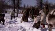 A young girl trudges through deep snow as men use shovels to make a clearing in the forest. Available in HD.