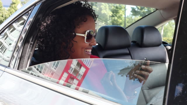 MS Young girl using cell phone in backseat of car smiling and having fun / Minneapolis, Minnesota, United States