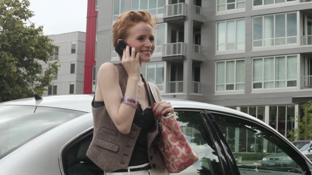 MS Young girl using cellular device outside next to her car on sunny day in urban area / Minneapolis, Minnesota, United States