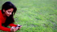 Young girl using smart phone in the park