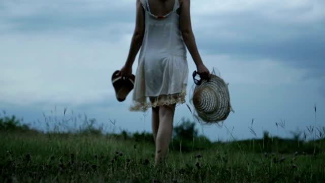 jong meisje lopen in een weide onder een bewolkte hemel