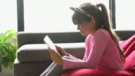 MS young girl watching a digital tablet at home.