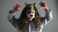 Young girl wearing tiger mask, roaring
